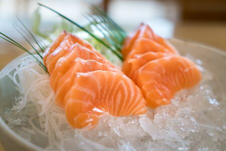 Raw salmon slice or salmon sashimi in Japanese style fresh serve on ice in bowl. Imagens