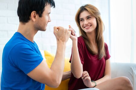 Couple hands show little finger on sofa in house. Romantic love concept. Hand to pinky swear, pinky promise hand signs.