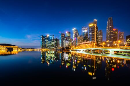 Singapore skyscraper building in downtown district with water reflection at Marina Bay in night, Singapore. Stock Photo