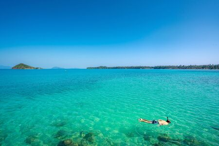 Tourists snorkel in crystal turquoise water near tropical resort in Phuket, Thailand. Summer, Vacation, Travel and Holiday concept. Imagens