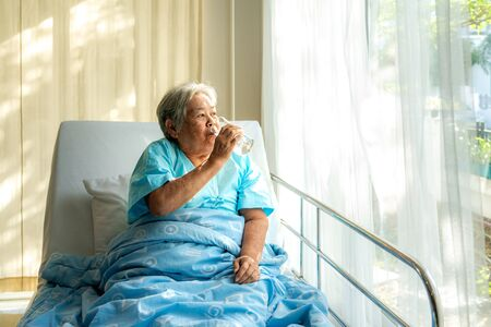 Asian elderly woman sitting and holding glass of water in bed at hospital. Reklamní fotografie