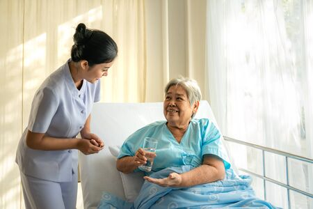 Asian nurse giving medication and glass of water to senior woman at hospital ward. Medicine, age, health care and people concept