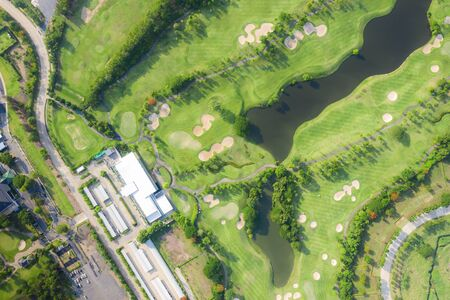 Aerial panoramic view of golf course and houses in city. Фото со стока