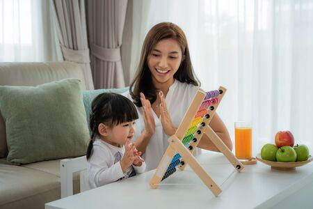 Felice giovane madre e figlia asiatiche che giocano con l'abaco, educazione precoce a casa.