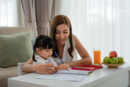 Asian mother playing with her toddler drawing together with color pencils at table in living room at home.