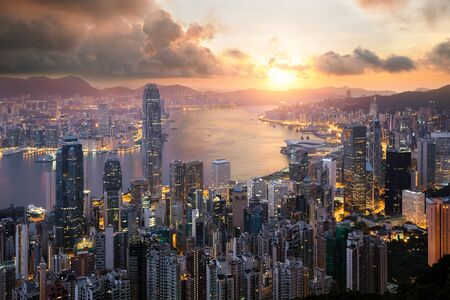 Sunrise over Hong Kong Victoria Harbor from Victoria Peak with Hong Kong and Kowloon below. Asian tourism, modern city life, or business finance and economy concept