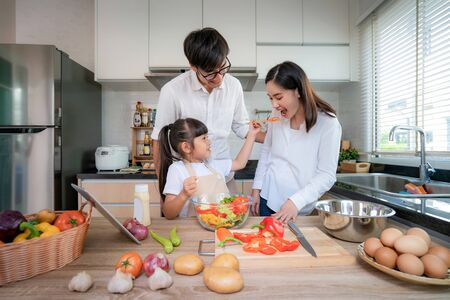 Asian daughters feeding salad to her mother and her father stand by when a family cooking in the kitchen at home.  Family life love relationship, or home fun leisure activity concept Standard-Bild