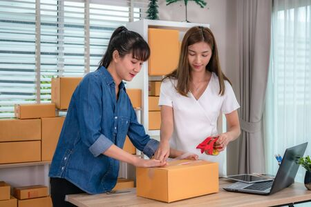 Two Asian teenager owner business woman work at home for online shopping, wrapping products with brown boxes  for delivery mail shipping with office equipment, entrepreneur lifestyle concept