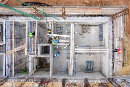 Aerial view of group of construction worker building in construction site.  Civil engineering, industrial development project, tower basement foundation infrastructure, or real estate property investm
