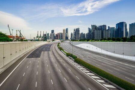 Skyline des Geschäftsviertels von Singapur mit touristischen Sehenswürdigkeiten mit leerer Straße an der Marina Bay, Singapur. Asiatischer Tourismus, modernes Stadtleben oder Geschäftsfinanzierungs- und Wirtschaftskonzept Standard-Bild