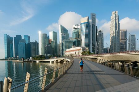 People jogging at morning in Singapore business district skyline financial downtown building with tourist sightseeing in day at Marina Bay, Singapore. Asian tourism, modern city life, or business finance and economy concept