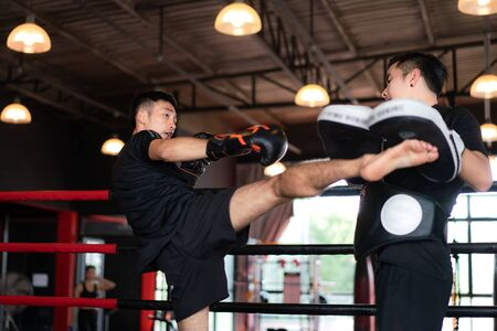 Young Asian Kick boxer kicking professional trainer in boxing studuim in the background at fitness gym. Boxer are hitting the sandbag for bodybuilding and healthy lifestyle concept.