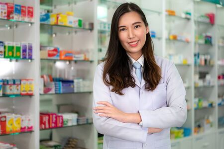 Confident Asian young female pharmacist with a lovely friendly smile standing with folded arms in the pharmacy drugstore. Medicine, pharmaceutics, health care and people concept.