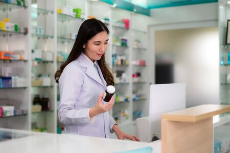 Confident Asian young female pharmacist with smile holding a medicine bottle and searching that product in the computer database in the pharmacy drugstore. Medicine, pharmaceutics, health care and people concept. Imagens - 132934043