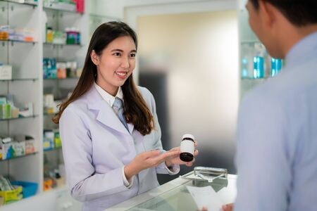 Confident Asian young female pharmacist with a lovely friendly smile and explaining medicine to her customer  in the pharmacy drugstore. Medicine, pharmaceutics, health care and people concept.