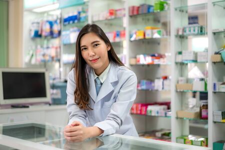 Confident Asian young female pharmacist with a lovely friendly smile standing leaning on a desk in the pharmacy drugstore. Medicine, pharmaceutics, health care and people concept. Imagens