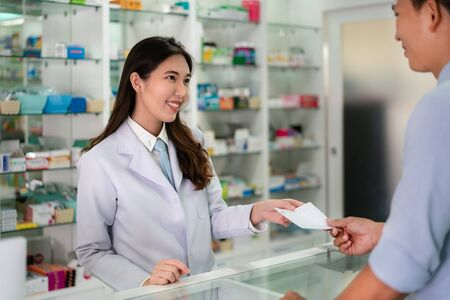 Confident Asian young female pharmacist with a lovely friendly smile and receive medicine prescription from man patient in the pharmacy drugstore. Medicine, pharmaceutics, health care and people concept.