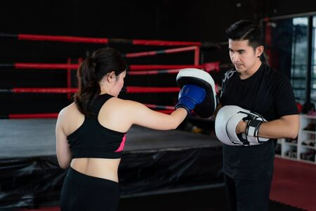 Young Asian woman boxer strikes with Straight punch to professional trainer in boxing studuim in the background at fitness gym. Sporty fit for healthy lifestyle Asian model of boxing gym concept.