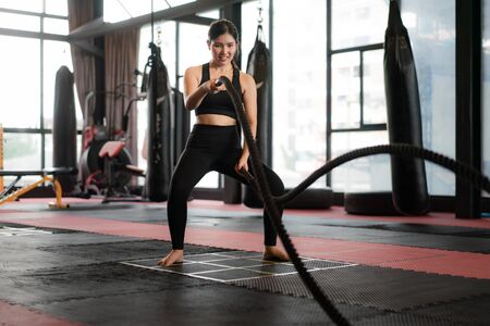 Beautiful Asian Woman with balck battle rope battle ropes exercise in the fitness gym with boxing bag in background. Sporty fit for healthy lifestyle Asian model of boxing gym concept.