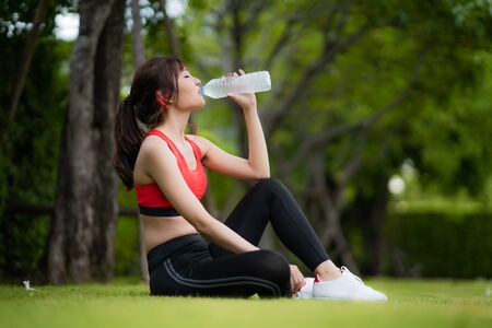 Asian beautiful woman sitting for relax after workout alone and drinking water from bottle in public park in village, happy and smile in morning during sunlight. Sport fitness model Asian ethnicity training outdoor concept.