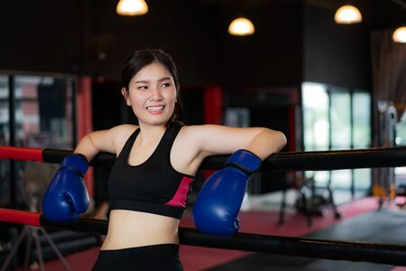 Tired Asian boxer sports girl leaned on black red ropes on boxing ring, and have a rest after hard training in black loft gym. Sporty fit for healthy lifestyle Asian model of boxing gym concept. 版權商用圖片