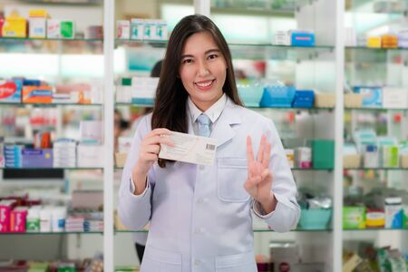 Asian young female pharmacist showing three finger explaining to her customer take a medicine three time or three capsule per day in the pharmacy drugstore. Medicine, pharmaceutics, health care and people concept. Imagens - 132934051