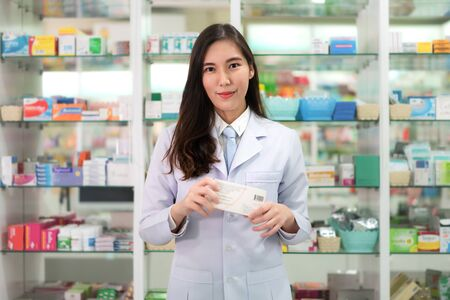 Asian young woman pharmacist with a lovely friendly smile holding medicinebox and looking at camera in the pharmacy drugstore. Medicine, pharmaceutics, health care and people concept.