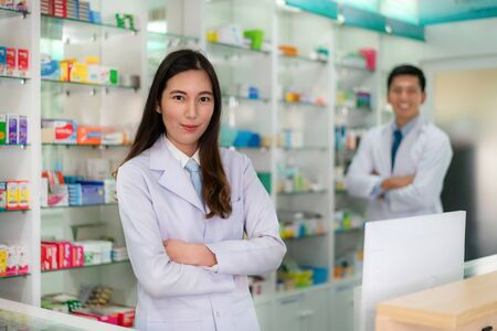 Two Asian young woman and man pharmacist with a lovely friendly smile standing with folded arms in the pharmacy drugstore. Medicine, pharmaceutics, health care and people concept.