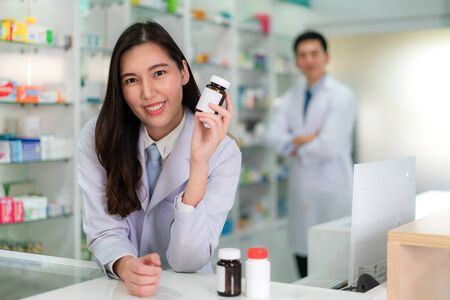 Two Asian young woman and man pharmacist with a lovely friendly smile holding medicine bottle and looking at camera in the pharmacy drugstore. Medicine, pharmaceutics, health care and people concept.