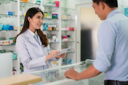 Confident Asian young female pharmacist with a lovely friendly smile and receive medicine prescription from man patient in the pharmacy drugstore. Medicine, pharmaceutics, health care and people concept. Imagens - 132934056