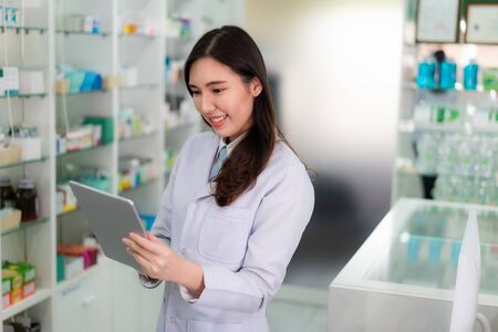 Confident Asian young female pharmacist with smile holding digital tablet and searching that product database in the pharmacy drugstore. Medicine, pharmaceutics, health care and people concept. Imagens - 132934057