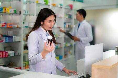 Confident Asian young female pharmacist with smile holding a medicine bottle and searching that product in the computer database in the pharmacy drugstore. Medicine, pharmaceutics, health care and people concept. Imagens - 132934059
