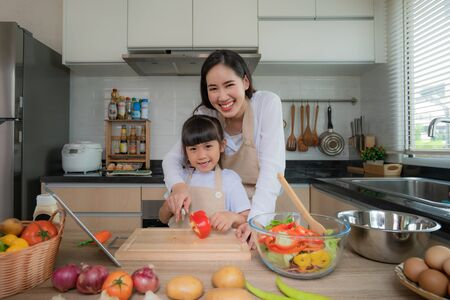Portrait of beautiful Asian young woman and her daughter cooking salad for lunch using online internet in a digital tablet seach recipe while making food, Family life love relationship, or home fun leisure activity concept