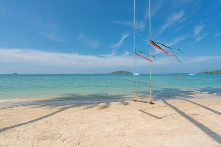 Swing hang from coconut palm tree over summer beach with clear water sea and wave with speed boat in background in Phuket, Thailand. Summer, Travel, Vacation and Holiday concept. Imagens - 132839508