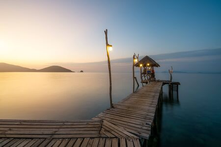 Wooden bar in sea and hut with clear sunrise sky in Koh Mak at Trat, Thailand. Summer, Travel, Vacation and Holiday. Relax and traveling at sea concept. Imagens - 132934236