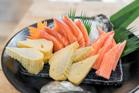 Japan raw salmon sashimi, sweet egg and imitation crab stick on ice pod in Japanese food restaurant. Japanese traditional food or with low calories and high nutrition and healthy diet dish. Imagens