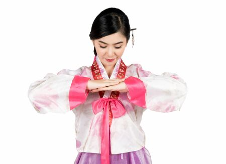 Portrait of young attractive Korean Woman with Hanbok, the traditional Korean dress smiling with white background  feeling confident and positive.