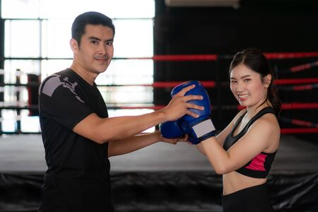 Young Asian woman boxer with professional trainer pose and smile at the camera during trainning in boxing studuim in the background at fitness gym. Sporty fit for healthy lifestyle Asian model of boxing gym concept. Imagens