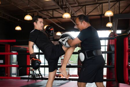Professional Asian Kick boxer strike with the right knee to professional trainer in boxing studuim in the background at fitness gym. Boxer are hitting the sandbag for bodybuilding and healthy lifestyle concept. Imagens - 132934486