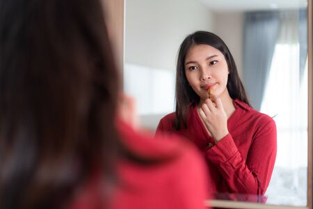 Beautiful Asian Woman wearing red dressed putting lipstick looking in mirror in her bedroom at home. Makeup in morning getting ready before going to work.