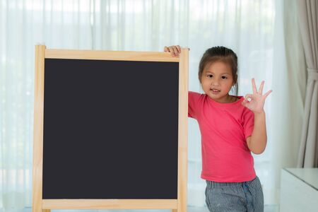 Asian Kindergarten girl child holding blackboard in school room looking happy with big smile doing ok sign, thumb up with fingers, excellent sign. Back to school and education concept.
