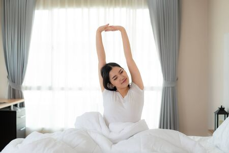 Beautiful Asian Woman stretching hands and body in bed after wake up in bedroom at home. Concept for start new day with happiness. Copyspace on the left. Young happy working female life Imagens