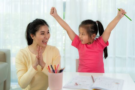 Happy successful Asian kindergarten student and her mother hands raised up to celebrate the successful to do homework in living room at home. Child art education or family love concept. Imagens - 133614337