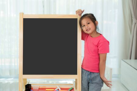 Asian Kindergarten girl child holding blackboard in school room looking happy with big smile. Back to school and education concept.