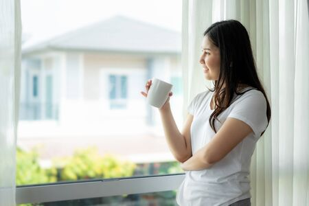 Beautiful Asian woman wake up in her bed fully rested and open the curtains on the windowsill and looking out the window with cup of coffee to get fresh air on sunshine in the morning in bedroom at home.