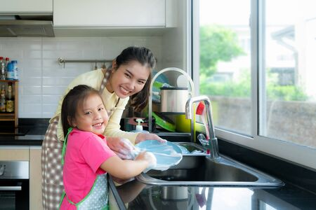 Beautiful Asian mother and daughter having fun while washing dishes together with detergent on sink in kitchen at home. Happy family time to teaching daughter to housework.