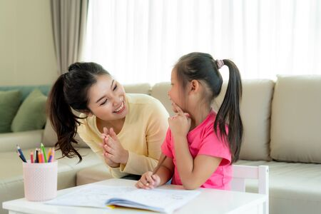 Asian mother playing with her daughter drawing together with color pencils at table in living room at home. Parenthood or love and bonding expression concept. Imagens - 133614349