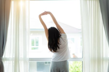 Rear view of Asian Woman stretching hands and body near window after wake up in bedroom at home. Concept for start new day with happiness. Young happy working female life Imagens