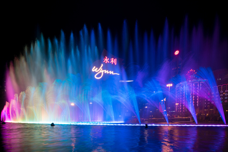 Macau, China - October 14, 2017 : Beautiful and very colorful city with lots of bright neon signs. Photo of the dancing fountain show at the famous Wynn hotel. Editorial