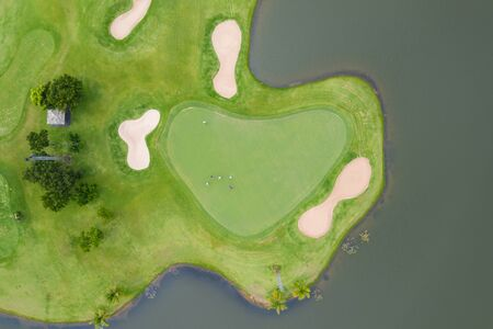 Aerial view of players on a green golf course. Golfer playing on putting green on a summer day. People lifestyle relaxing time in sport field or vacation outdoors activity. Imagens - 133870991